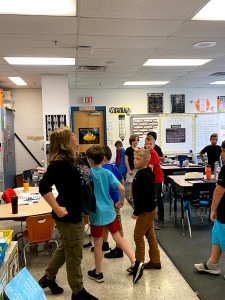 A Teaching Artist and young students in class walking as if they are carrying heavy armor on their bodies.